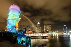 Nacht Lichte Merlion met Stadsmening Stock Foto's
