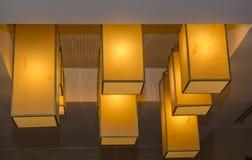 Nacht modieuze moderne, rechthoekige warme lichten die uit van plafond in woonkamer hangen Royalty-vrije Stock Foto