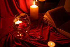 Nacht rood stilleven met kaarsen, een roos, een boek en een verslag Royalty-vrije Stock Afbeeldingen