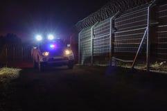 Nacht, Sicherheitsstreifenwagen, der entlang den Zaun sich bewegt Stockfoto