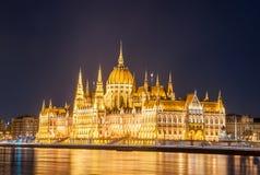 Nachtansicht des ungarischen Parlaments-Gebäudes auf der Bank der Donaus in Budapest Stockfotos