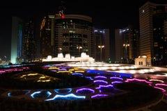 Nachtansicht von bunten Brunnen und von Wolkenkratzern in Abu Dhabi, Vereinigte Arabische Emirate Lizenzfreie Stockbilder