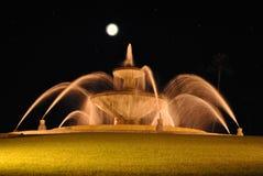Nachtaufnahme des Brunnens mit unscharfem Wasser und Vollmond und Sterne lizenzfreies stockfoto