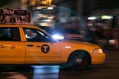 Nachtaufnahme eines gelben Fahrerhauses in Manhattan in der Bewegungsunschärfe Lizenzfreies Stockfoto