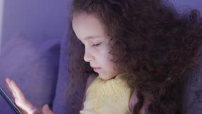 Nachtaufnahme-Porträt eines kaukasischen netten Kindes, kleiner Baby-Abschluss oben einer Kindergesicht-Betrachtung ein Tablet-PC stock video