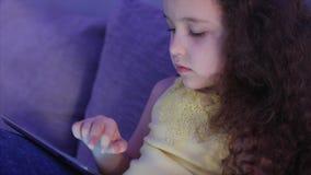 Nachtaufnahme-Porträt eines kaukasischen netten Kindes, kleiner Baby-Abschluss oben einer Kindergesicht-Betrachtung ein Tablet-PC stock footage