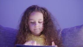 Nachtaufnahme-Porträt eines kaukasischen netten Kindes, kleiner Baby-Abschluss oben einer Kindergesicht-Betrachtung ein Tablet-PC stock video footage