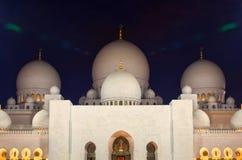 Nachtaufnahme von belichtetem Zayed Mosque in Abu Dhabi mit weißen Marmorhauben Lizenzfreie Stockfotos