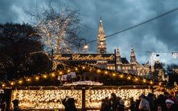 Nachtaufnahme von Weihnachtsmärkten bei Rathausplatz, das Text Wiener Würstchen Christkindlmarkt, Rathaus im Hintergrund stockfoto