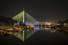 Nachtbeeld van de brug op ada met bezinning in het duidelijke water terwijl de verlichting overloopt royalty-vrije stock fotografie