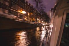 Nachtbeleuchtungsreflexionen in Amsterdam-Kanälen von beweglichem Kreuzfahrtboot Unscharfes abstraktes Foto als Hintergrund Stockfotografie