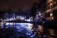 Nachtbeleuchtungsreflexionen in Amsterdam-Kanälen von beweglichem Kreuzfahrtboot Unscharfes abstraktes Foto als Hintergrund Lizenzfreie Stockbilder