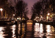 Nachtbeleuchtungsreflexionen in Amsterdam-Kanälen von beweglichem Kreuzfahrtboot Unscharfes abstraktes Foto als Hintergrund Stockbild