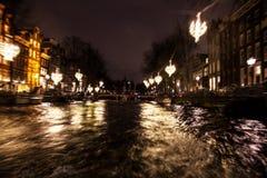 Nachtbeleuchtungsreflexionen in Amsterdam-Kanälen von beweglichem Kreuzfahrtboot Unscharfes abstraktes Foto als Hintergrund Lizenzfreie Stockfotos