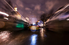 Nachtbeleuchtungsreflexionen in Amsterdam-Kanälen von beweglichem Kreuzfahrtboot Unscharfes abstraktes Foto als Hintergrund Stockfotos