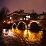 Nachtbeleuchtungsreflexionen in Amsterdam-Kanälen von beweglichem Kreuzfahrtboot Unscharfes abstraktes Foto als Hintergrund Lizenzfreies Stockfoto