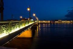 Nachtbrücke über einem breiten Fluss am Abend stockbild