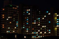Nachtbunte Fensterlichter im Wohngebäude Stockbild