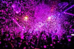Nachtclub-Schattenbildmenge übergibt oben in Konfettidampfstadium stockfotos