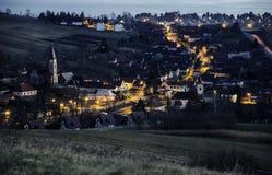 Nachtdorf nach Sonnenuntergang in der dominierenden Kirche nahe ¡ Liptovsky MikulaÅ Stockfotos