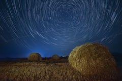Nachtfoto mit Stern kreist auf dem Feld mit Heuschobern ein Stockfotografie