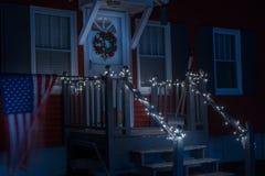 Nachtfoto van de portiek van een klein eenvoudig huis dat met Kerstmisslingers en een kroon wordt verfraaid De vlag van Amerika o stock foto