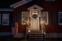 Nachtfoto van de portiek van een klein eenvoudig huis dat met Kerstmisslingers en een kroon wordt verfraaid De vlag van Amerika o royalty-vrije stock afbeelding