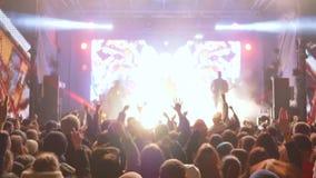 Nachtgebeurtenis, menigte van springende ventilators met handen op verrukkingsprestaties van rotsmusicus op levendige scène stock footage