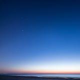 Nachthemel met sterren op het strand Bevolen aantal gebieden bij de horizon van belangrijke blauwe planeet Stock Foto's