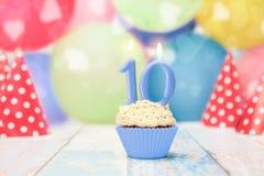 Nachtisch des kleinen Kuchens für zehnten Geburtstag mit Parteihüten stockbild