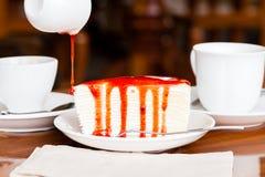 Nachtisch - gießen Sie roten Sirup auf Käsekuchen Lizenzfreie Stockbilder