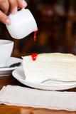 Nachtisch - gießen Sie roten Sirup auf Käsekuchen Stockfotos