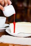 Nachtisch - gießen Sie roten Sirup auf Käsekuchen Stockfotografie