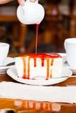 Nachtisch - gießen Sie roten Sirup auf Käsekuchen Lizenzfreies Stockbild
