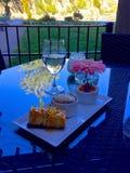 Nachtisch, Glas Wasser und eine Blume auf dem Tisch mit einer Ansicht Lizenzfreies Stockbild