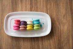 Nachtisch-Makrone gelegt in einen Teller mit einem hölzernen Hintergrund Stockfotografie
