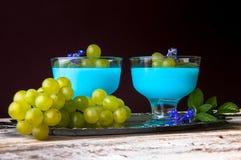 Nachtisch mit blauem Gelee und Trauben Stockfotografie