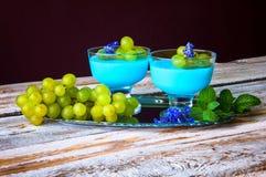 Nachtisch mit blauem Gelee und Trauben Stockfotos
