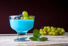 Nachtisch mit blauem Gelee und Trauben Stockbilder