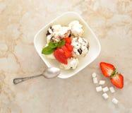 Nachtisch mit Eiscreme und Erdbeeren mit Schokolade Stockfotografie