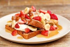 Nachtisch routons mit Erdbeeren, Bananen und Eiscreme mit Honig Lizenzfreie Stockbilder