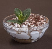 Nachtisch Tiramisu mit Schokolade und tadellosen Blättern in einer runden Glasform Stockfoto