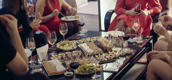 Nachtischbuffet mit den Wein umgebenen weiblichen Beinen Stockfotografie
