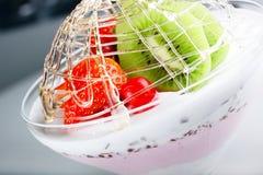 Nachtischeiscreme mit einer Erdbeere und einer Kiwi Lizenzfreies Stockfoto