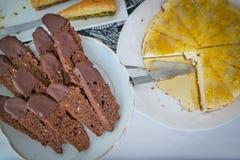 Nachtischtabelle mit Schokolade biscotti und Käsekuchen auf Weiß Stockbilder