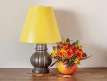Nachtlamp en Bloemen in een Pompoen op een Houten Opmaker royalty-vrije stock afbeelding