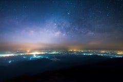 Nachtlandschaft der Milchstraße über dem Licht des Landschaftsbereichs und -berges Stockfotos