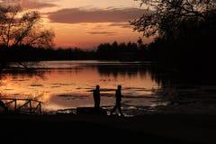 Nachtlandschaft - die Satzsonne im Abendhimmel über dem See, der Schattenbilder von Bäumen reflektiert Lizenzfreies Stockfoto
