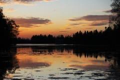 Nachtlandschaft - die Satzsonne im Abendhimmel über dem See, der Schattenbilder von Bäumen reflektiert Lizenzfreie Stockbilder