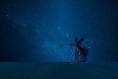Nachtlandschaft mit alter Windmühle und Sternen Stockbilder